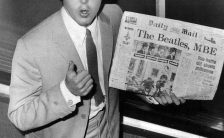 Paul McCartney with the Daily Mail newspaper bearing a headline about The Beatles' MBEs, 11 June 1965
