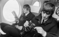 eight_col_Beatles_Ringo_Starr_and_George_Harrison_on_a_plane_with_book_and_camera_by_Morrie_Hill_courtesy_ATL.jpg